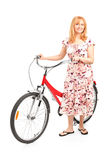 Mature female posing next to a bicycle Stock Photography