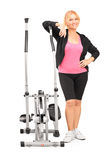 Mature female posing next to a cross trainer Royalty Free Stock Image