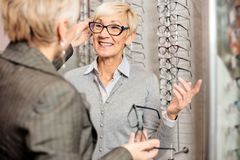 Mature female seller helping smiling senior woman to choose prescription glasses in optician store royalty free stock photo