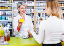 Mature female seller suggesting care products to young customer. Glad positive mature female seller suggesting care products to young customer in specialized stock photography