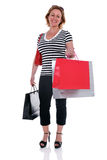 Mature female shopper carrying shopping bags . Stock Image