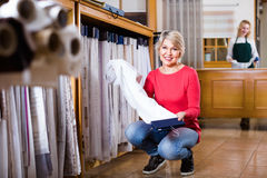 Mature female shopper searching for suitable fabric. Happy cheerful smiling  mature female shopper searching for suitable fabric in textile shop Royalty Free Stock Images