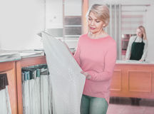 Mature female shopper searching for suitable fabric. Happy mature female shopper searching for suitable fabric in textile shop Royalty Free Stock Photo