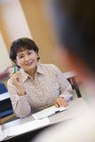 Mature female student raising hand in class Royalty Free Stock Photography