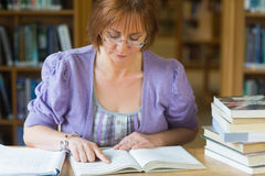 Mature female student studying at desk in the library Stock Photo