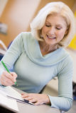 Mature female student writing in class Royalty Free Stock Image