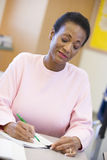 Mature female student writing in class Royalty Free Stock Photos