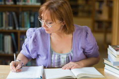 Mature female student writing notes at desk in the library Stock Photos