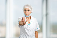 Mature female surgeon gesturing stop. Royalty Free Stock Images