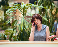 Mature female talking smartphone Stock Photos
