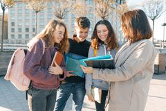 Mature female teacher talking to teenage students outside of school, golden hour stock photos