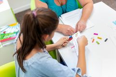 Mature female therapist working with a teenage girl with learning difficulties to master logical tests. Mature female therapist working with a teenage girl with royalty free stock photography