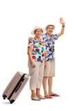 Mature female tourist with suitcase and mature male tourist waving. Full length portrait of a mature female tourist with a suitcase and a mature male tourist stock photography