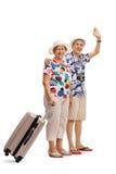 Mature female tourist with suitcase and mature male tourist wavi Stock Photography