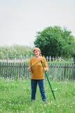 Mature female worker sharpening the scythe royalty free stock image
