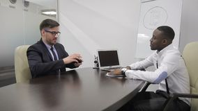 Mature financial analytic is having a job interview with african boss of bitcoin investment start-up.