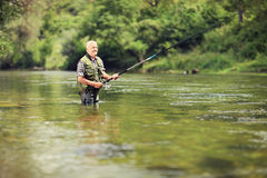 Mature fisherman fishing in a river Stock Images