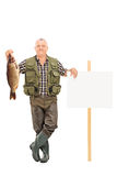 Mature fisherman holding a big fish next to a panel Stock Photo