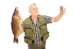 Mature fisherman holding a fish and taking selfie Royalty Free Stock Images
