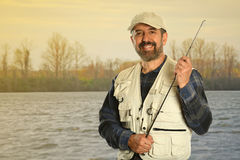 Mature Fisherman by Lake. Mature Hispanic fisherman smiling next to lake at sunrise stock photo
