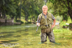 Mature fisherman posing with fishing rod in river Royalty Free Stock Photos