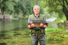 Mature fisherman standing in river and holding fish Stock Photo