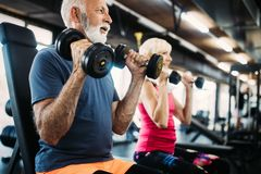 Senior fit man and woman doing exercises in gym to stay healthy stock image