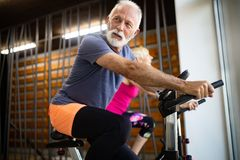 Mature fit people biking in the gym, exercising legs doing cardio workout cycling bikes stock images