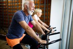 Mature fit people biking in the gym, exercising legs doing cardio workout cycling bikes royalty free stock image