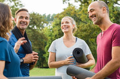 Mature fitness friends talking. Happy multiethnic group of mature people holding yoga mat and towel in conversation after exercising at park. Happy senior men Royalty Free Stock Photography