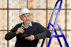 Mature foreman looking upwards. Elderly engineer checking the construction with clipboard, ladder, blurred background stock photography