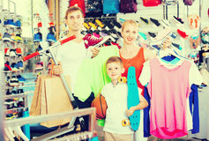 Mature friendly parents with boy in sport store Royalty Free Stock Image