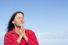 Mature friendly woman Meditating and praying. Portrait attractive mature woman relaxed, concentrated, closed eyes, smiling friendly, praying, with folded hands Royalty Free Stock Photos
