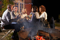 Mature Friends Enjoying Outdoor Evening Meal Around Firepit Royalty Free Stock Image