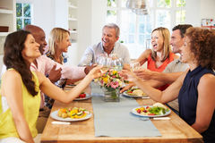 Mature Friends Sitting Around Table At Dinner Party Royalty Free Stock Image