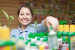 Mature gardener chooses liquid fertilizer. Female mature gardener chooses liquid fertilizer  at store for gardeners Stock Photo