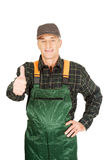 Mature gardener in uniform with thumbs up Royalty Free Stock Image