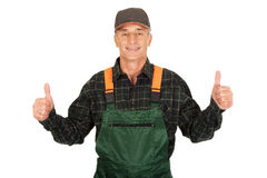 Mature gardener in uniform with thumbs up Stock Photography