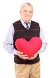 Mature gentleman holding a red heart Stock Photos