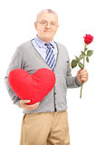 Mature gentleman holding a red heart and flower Stock Photography