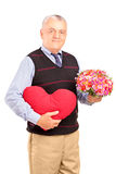 A mature gentleman holding a red heart and flowers Stock Photos