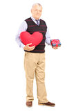 Mature gentleman holding a red heart and gift Royalty Free Stock Images