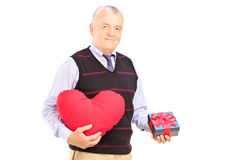 Mature gentleman holding a red heart and gift Stock Images