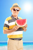 Mature gentleman holding a slice of watermelon on a beach Stock Photo