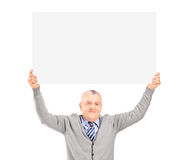 Mature gentleman sitting and holding a blank panel above his hea Stock Photo