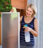 Mature girl cleaning glass door Stock Photos
