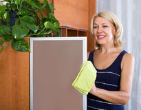 Mature girl cleaning glass door Royalty Free Stock Photography