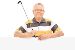 Mature golf player standing behind a panel Stock Images