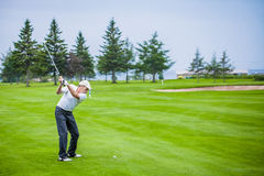 Mature Golfer on a Golf Course. Taking a Swing in the Fairway Royalty Free Stock Photography