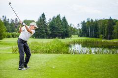 Mature Golfer on a Golf Course. Taking a Swing on the Start Royalty Free Stock Photography